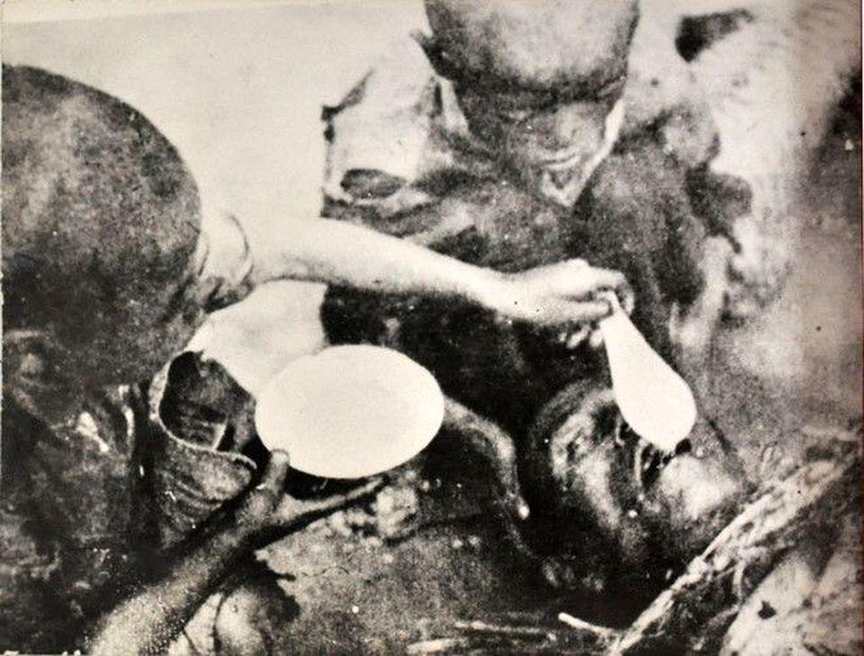 Ayant pu obtenir de la bouillie, ces deux enfants ont essayé d'en verser dans la bouche de leur papa, mais elle a coulé parce que la machoire était durcie. Photo prise à Phu Ly, Ha Nam par Vo An Ninh
